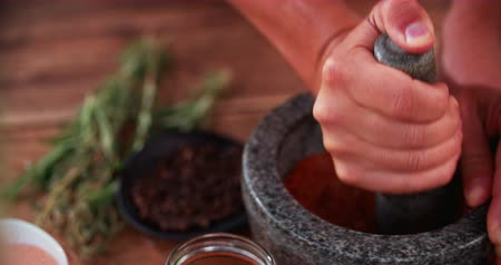 temperos : Chefs hands using a stone mortar and pestle to confidently grind a selection of herbs and spices while making a dry meat rub seasoning Stock Footage