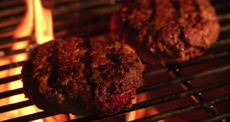 пламя : Home made beef burger patties being flame-grilled on the grill of a night time barbecue in Slow Motion
