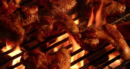 grelha : Temptingly spicy chicken wings being grilled over the bright glowing coals of a night time barbecue in Slow Motion