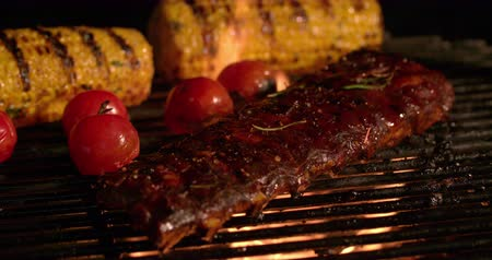costela : Night time barbecue with tender ribs, small tomatoes and corn grilling over the glowing coals in Slow Motion