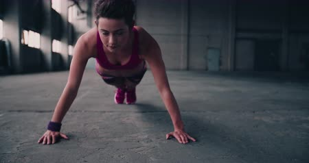 fit : Pretty woman looking at the camera while doing push ups in a grungy space with a concrete floor in Slow Motion