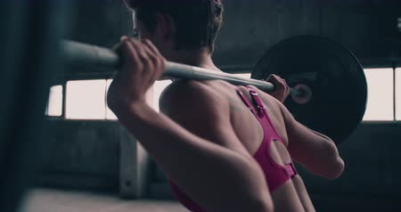 musculação : rearview image of a girl wearing sportswear lifting a heavily weighted barbell