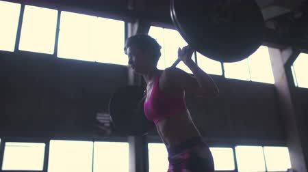 musculação : Woman lifting a barbell with heavy weights in a grungy industrial setting