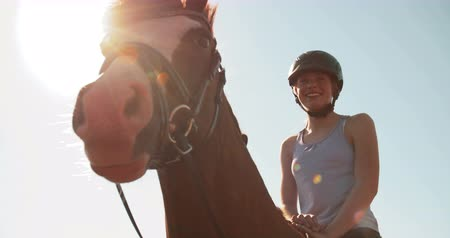 helmets : Low angle shot of a teen girl wearing a helmet and smiling while riding her horse outdoors with a bright blue sky in the background