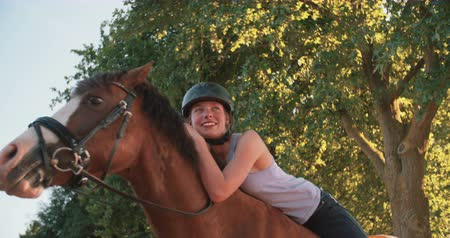 helmets : Smiling girl lovingly leaning on her beautiful horse with a white face and brown body while outdoors in nature on a tranquil day in Slow Motion