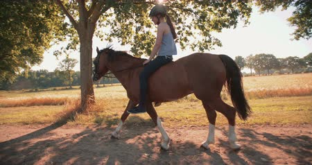 horse riding : Full length image of a smiling teen girl peacefully riding a beautiful horse on a path under leafy trees alongside a sunlit field, Slow Motion