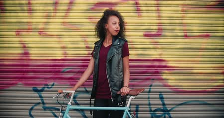 african decent : Teenage African American girl standing on a sidewalk in front of urban graffitti with her vintage bicycle