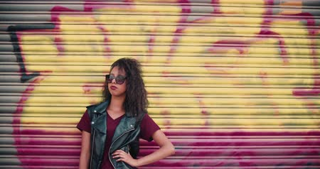 african decent : Low angle shot of an African American teenage girl standing against an urban garage door painted with graffitti looking confident and wearing sunglasses and a leather jacket