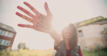 Closeup of a teenage girls hand with the phrase Believe in your Dreams written in permanent marker on it, with her smiling face blurred in the background Стоковые видеозаписи