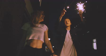 unrecognizable people : Young couple walking in Slow Motion close together on a city street at night while celebrating with sparklers