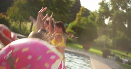 candid laughter : Teen friends jumping into a summer pool in Slow Motion and each of them holding a pool inflatable