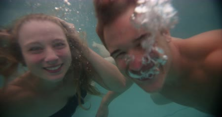 basen : Young couple swimming together underwater and having fun in a pool in Slow Motion
