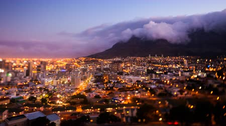 güney : Timelapse of Cape Town and the Table Mountain during sunset and nightfall, all city lights illuminated and the signature tablecloth clouds coming over the mountain