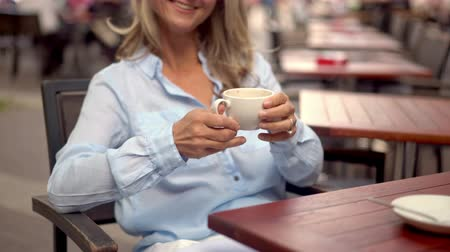 diferansiyel odak : Cropped image of a smiling mature woman holding a fresh cup of coffee while sitting at an outdoor cafe