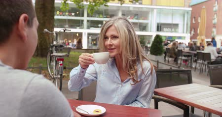 диалог : Smiling mature woman enjoying a cup of coffee at an outdoor cafe with a young man in town