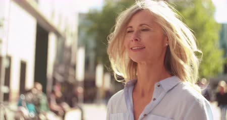 gyalogút : Smiling mature woman with grey hair walking confidently down a city street while holding shopping bags