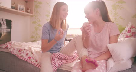 boldogság : Smiling adolescent friends sitting on a bed together in a pleasant bedroom sharing a pot of nail varnish while having fun grooming together in Slow Motion