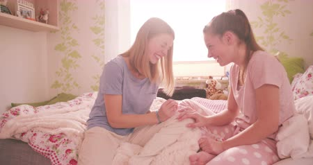pajama : Smiling adolescent girl sitting with her friend on her bed giving her a manicure at a pyjama party in a sunlit bedroom Stock Footage