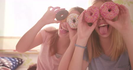 amigos : Two adolescent girl friends having a pyjama party in a sunny bedroom holding colourful doughnuts up to their faces to cover their eyes while sticking out their tongues at the camera