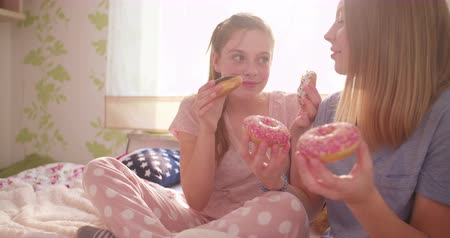 amigos : Two teen girl friends laughing and sharing doughnuts while having a pyjama party in a bright and colourful bedroom Vídeos