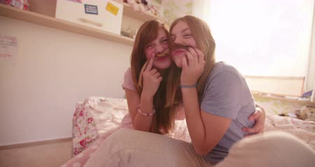 pajama : Teen girls sitting together on a bed in their pyjamas holding each others hair up to their faces as moustaches while having a fun daytime pyjama party