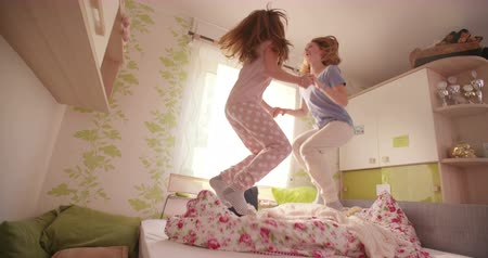 jump : Teen girls who are best friends jumping wildly together holding hands on a bed and wearing pyjamas Stock Footage