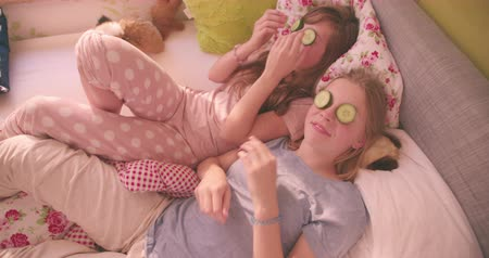 pajama : Two teen girl friends in their pyjamas lying on a bed in a colourful bedroom holding slices of cucumber and laughing and smiling Stock Footage