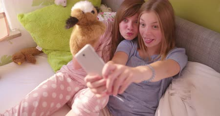 tongue out : Fun adolescent girl friends posing with their tongues sticking out for a silly selfie together with one girl holding a soft puppet up in a colourful sunlit bedroom