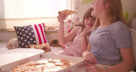 paylaşımı : Teen girl feeding her laughing friend a huge slice of cheesy pizza while sitting in bed having and afternoon pyjama party in a sunlit bedroom