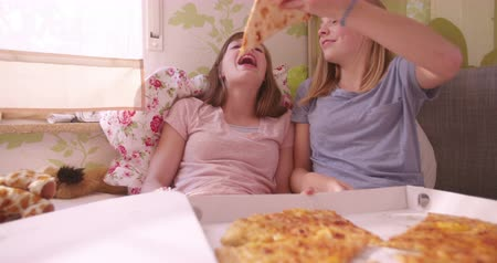 étkezik : Adolescent girls having a fun pyjama party and joking, with one girl holding a huge slice of pizza up in the air and feeding it to her friend