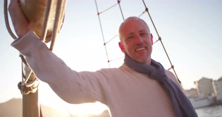holding onto : Handsome adventure mature man on yacht in picturesque sunset holding onto the mast
