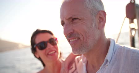 żaglowiec : Close up shot of a retired couple looking lovingly at the ocean while enjoying a cruise on a yacht with clear blue sky and bright afternoon sunflare Wideo