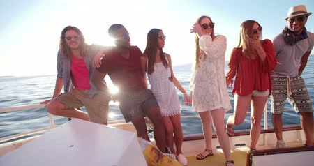 african decent : Group of multi ethnic friends standing close to each other  on a yacht  and posing for a group portrait at sunset