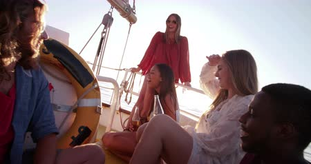 destinos : Group of girl friends happy and relaxing on a golden summer evening, enjoying a sunset cruise on a yacht while drinking beer with brilliant sunflare Stock Footage