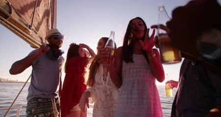 african decent : Group of friends enjoying a party on a yacht, laughing and dancing while holding drinks at sunset with golden sunflare in Slow Motion