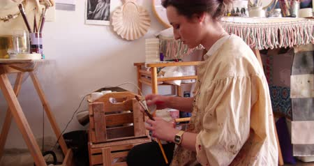 zanaat : artist holding some paint brushes and checking her paint by putting the brushes in Stok Video