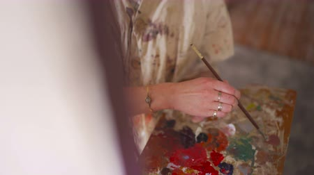 hiteles : Vintage themed image of a young woman artist  wearing a well worn old-fashioned artists smock covered with paintwhile working with a fine brush on a canvas in her studio Stock mozgókép