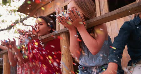 african decent : Multi ethnic group of children blowing confetti in treehouse in Slow Motion on a sunny day in park