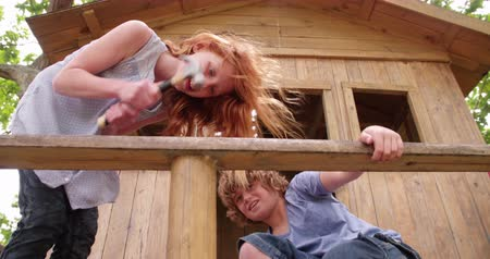 молоток : Friends who are children working together to build a treehouse, hammering, helping and sawing on a summer day