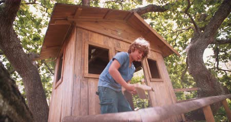 piloto : Young boy in a rustic wooden treehouse surrounded by lush green leaves, playing happily with a toy airplane made from wood Stock Footage