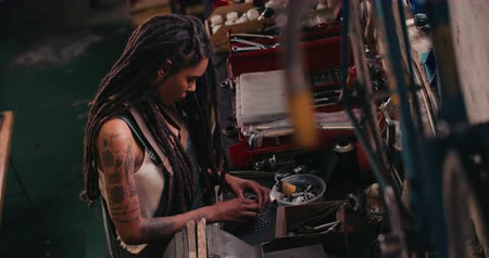 raszta : High angle image of an afro-american craftswoman working carefully at her work bench  surrounded by well-used tools, assembling bicycle parts