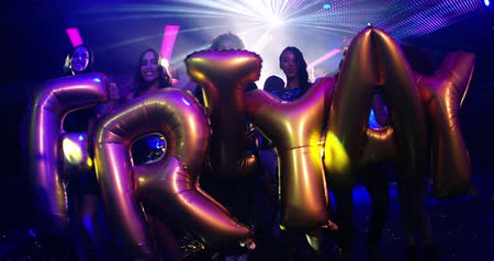 yeah : A cheerful group of young party girls and teenagers holding inflatableballoon words spelling out friyay in a popular trendy nightclub.