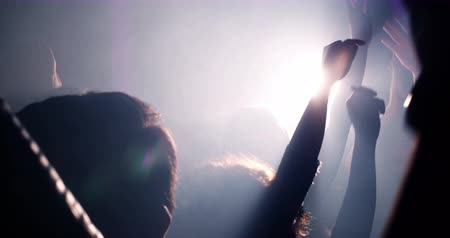 koncert : Slow mortion shot of young festive people with their hands raised and in the air at concert or party. Smoke is lingering in the nightclub and silhouettes of teenagers dancing.
