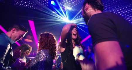 Attractive young Brazilian woman dancing with a group of friends in the background at a party in a modern night club