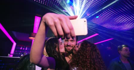 bochecha : Joyful attractive young multi-ethnic group at nightclub party taking selfies while dancing and smiling for the photo with all the cool music and disco lights in the background