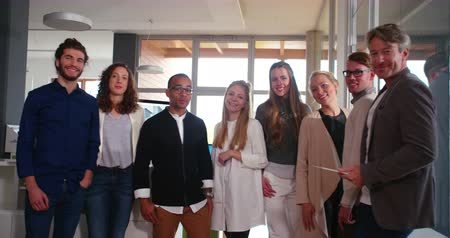 multikulturális : Group of young startup professionals posing with their business executive after a succesful presentation at a modern design studio office.