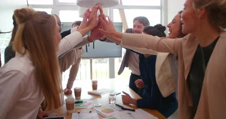 jovem : Young creative team and mature team leader giving high fives to one another after successful business meeting in meeting rooom