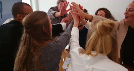 dosažení : Young creative team and mature team leader giving high five to one another after successful business meeting in meeting rooom