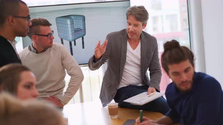 Mature man explaining notes to young multi-ethnic team members on the presentation he had given on the television, while team members listen intently