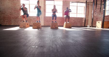 tornaterem : Multi-ethnic group of teen friends jumping onto wooden boxes in a crossfit workout Stock mozgókép